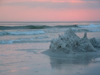 a rock formation in the splashing waves at sunset