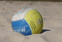 A blue, white, and yellow volleyball lies partially buried in the sand
