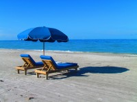 two blue lounge chairs set on a sandy white beach with an umbrella casting a shadow towards the water