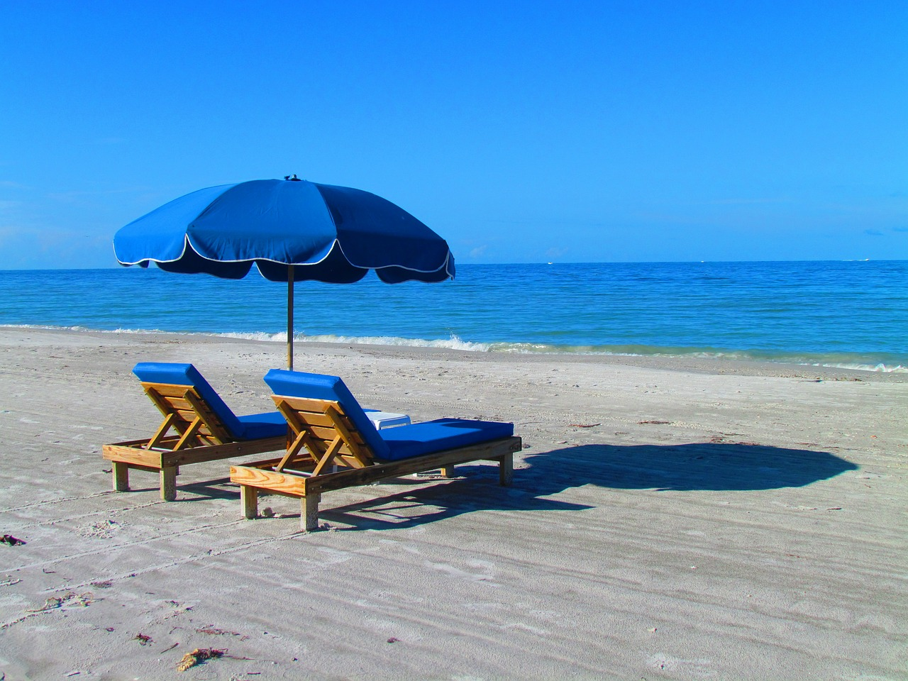 Two Blue Lounge Chairs Set On A Sandy White Beach With An Umbrella Casting  A Shadow