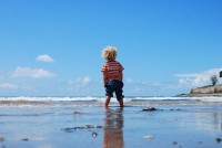A small child with blond curly hair faces away from the camera on a beach
