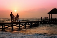 A family of four stand on a pier over the ocean, backlit by the setting sun.