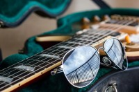 A pair of sunglasses rests against the neck of a guitar in the sand.