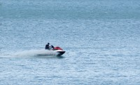 A single rider on a Jet Ski on a blue expanse of water