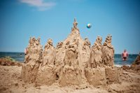 An elaborate sandcastle with a blue sky in the background