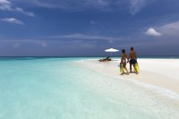 A couple walks along a white sand beach next to turquoise water