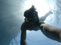 A man snorkels in blue water with the sun behind him. His arm is outstretched toward the camera